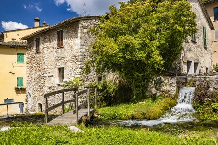 The small village of Rasiglia, crossed by many streams and waterfalls, fed by the Menotre river. A sluice regulates the flow of water. A wooden bridge. Old brick houses. Foligno, Umbria. Banco de Imagens - 148814031