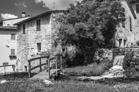 The small village of Rasiglia, crossed by many streams and waterfalls, fed by the Menotre river. A sluice regulates the flow of water. A wooden bridge. Old brick houses. Foligno, Umbria.