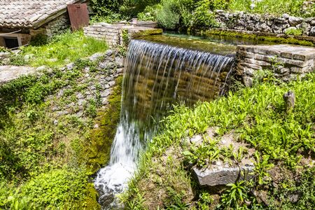 A small waterfall in the village of Rasiglia, crossed by many streams, fed by the Menotre river. A sluice regulates the flow of water. Lush vegetation among the rocks. Foligno, Umbria.