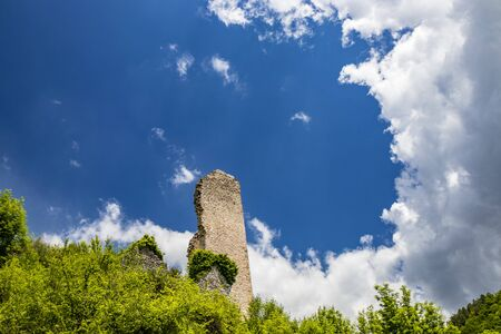 The ruin of the keep of the Trinci castle in Rasiglia. The remains of the tower, covered by vegetation, now collapsed and almost completely destroyed. The blue sky with clouds. Foligno, Umbria, Italy