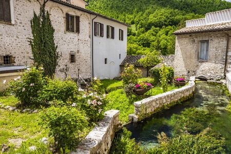 The small village of Rasiglia, crossed by numerous streams and canals. A sluice regulates the flow of water. Well-kept garden full of flowers. Old brick houses. Foligno, Umbria, Italy Banco de Imagens