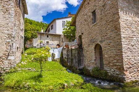 The small village of Rasiglia, crossed by many streams and waterfalls, fed by the Menotre river. A sluice regulates the flow of water. Blooming white roses. Old brick houses. Foligno, Umbria.