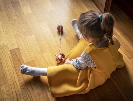 The original Kendama. An ancient, traditional, wooden Japanese skill toy for children. Has three cups, spike and ball. A little girl dressed in yellow plays with the kendama, at home, on the parquet. Reklamní fotografie