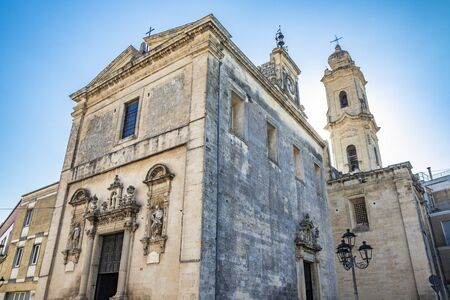 The mother church of Cavallino, Lecce, Puglia, Salento, Italy. In baroque style. Wooden portal and niches with statues on the sides, on the facade. Stock Photo