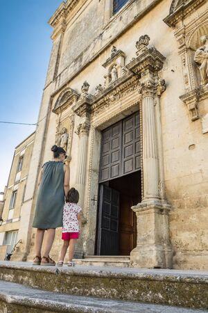 A mother and her child climb the steps and enter the church of Cavallino, Lecce, Puglia, Salento, Italy. In baroque style. Wooden portal with statues on the sides, onthe facade. Stock Photo