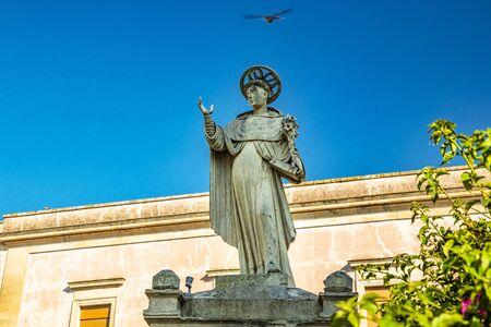 The well with the statue of the Saint Protector San Domenico di Guzman in Cavallino, Lecce, Puglia, Salento, Italy. Stok Fotoğraf