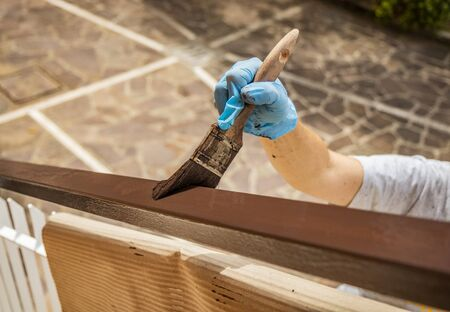 A woman / man painting and renovating the iron railing, white and brown, of her home. Do it yourself for economic savings. Made in Italy. Detail, close-up of the brush in his hand with blue glove. Foto de archivo