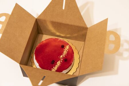 unboxing a cheesecake from its packaging. Cheesecake with red jam with berries and raspberries. On a white table, brown box.