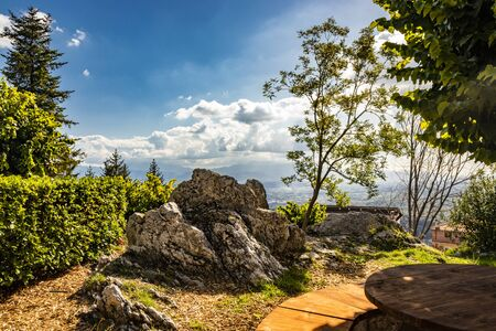 Bellegra, Rome, Lazio, Italy - The panorama seen from Bellegra. The cloudy blue sky. Mountains and sunbeams. Glimpse of a public garden, with trees and spikes of rock. Bench with wooden table. Imagens