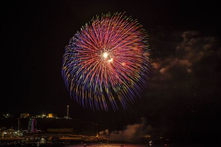 Beautiful fireworks in Santa Maria di Leuca, on the night of August 15th, in the summer holidays. Flashes of the colored fires are reflected on the sea. Boats watch the show. Puglia, Salento, Italy. Stock Photo