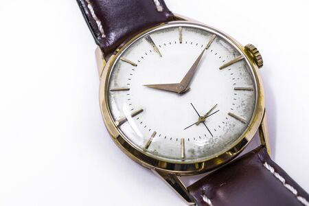 An old gold mechanical wristwatch with manual winding. Antique watch ruined by time, with scratches and mildew stains, rust, oxidation. Leather strap (band). Vintage clock. Spend time. Standard-Bild