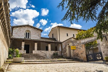 The Church of San Severino. The porch, the mullioned window, the cross, the medieval walls. In Spello, province of Perugia, Umbria, Italy. Stock Photo