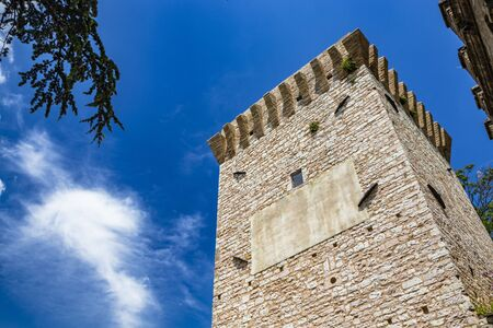 The tower and the medieval walls, in stone and brick, with merlon. In Spello, province of Perugia, Umbria, Italy.