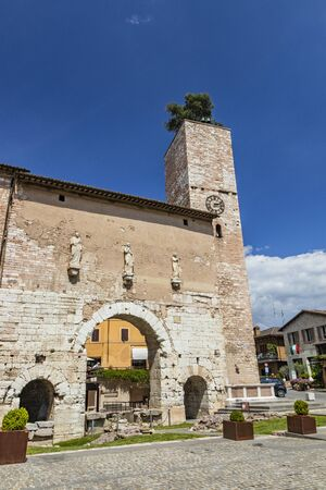 The Roman consular door, with the tower and the clock. One of the accesses to the city walls. Three statues above the arch. In Spello, province of Perugia, Umbria, Italy. Stock Photo