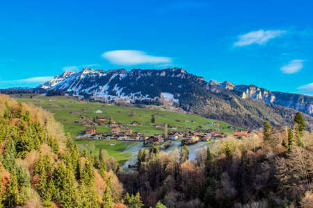 spectacular view of the snow-capped mountains in winter at Sigriswil in the district of Thun - Bern, Switzerland. Panorama with houses, grass, green, trees, forest, nature, vegetation, lake, water Stock Photo