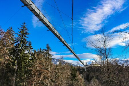 a spectacular suspension bridge (pedestrian), in iron, in the municipality of Sigriswil, in the district of Thun in the canton of Bern, Switzerland. View of mountains and lake in winter. 版權商用圖片