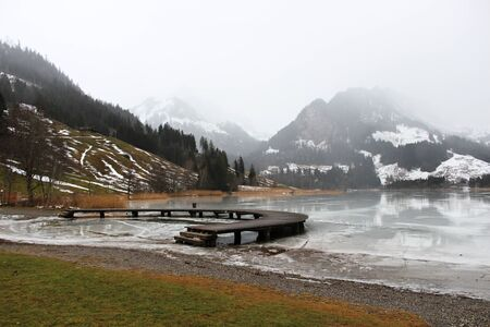 Schwarzsee or Lac Noir (Black Lake) is a small lake in the Canton of Friborg, Switzerland. Wooden jetty on the frozen lake, immersed in the mist, among the snow-capped mountains Foto de archivo - 149586234