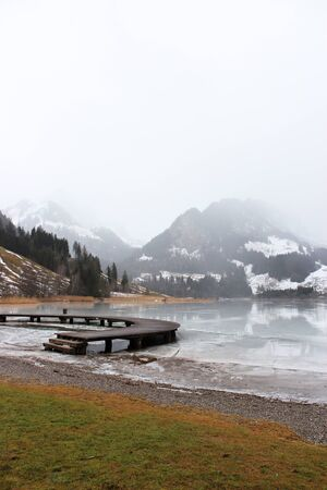 Schwarzsee or Lac Noir (Black Lake) is a small lake in the Canton of Friborg, Switzerland. Wooden jetty on the frozen lake, immersed in the mist, among the snow-capped mountains Foto de archivo