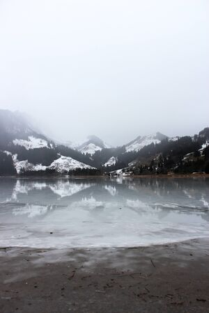 Schwarzsee or Lac Noir (Black Lake) is a small lake in the Canton of Friborg, Switzerland. The frozen lake, immersed in the mist, among the snow-capped mountains Foto de archivo - 149585178