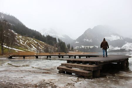 Schwarzsee or Lac Noir (Black Lake) is a small lake in the Canton of Friborg, Switzerland. Wooden jetty on the frozen lake, immersed in the mist, among the snow-capped mountains Foto de archivo - 149585361