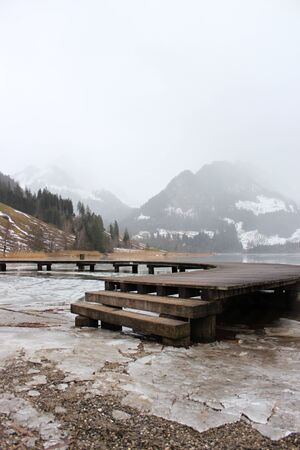 Schwarzsee or Lac Noir (Black Lake) is a small lake in the Canton of Friborg, Switzerland. Wooden jetty on the frozen lake, immersed in the mist, among the snow-capped mountains Foto de archivo - 149585576