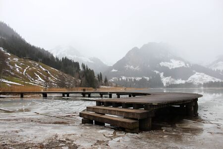 Schwarzsee or Lac Noir (Black Lake) is a small lake in the Canton of Friborg, Switzerland. Wooden jetty on the frozen lake, immersed in the mist, among the snow-capped mountains Foto de archivo - 149585697