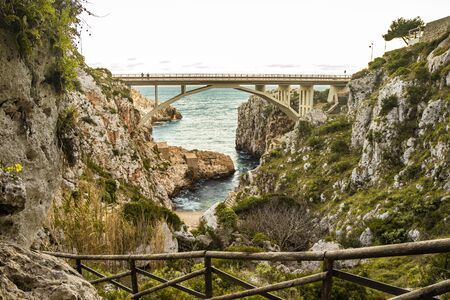 The Ciolo bridge connects two high cliffs. An inlet of the sea, in Gagliano del Capo, near Santa Maria di Leuca. The red and orange sunset. On a winter evening. Salento, Puglia, Italy.