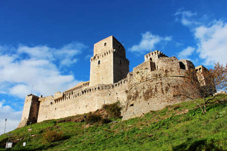 The ruins of the medieval castle of Assisi, in Umbria, Perugia, Italy. The fortress with towers, made of brick and stone.