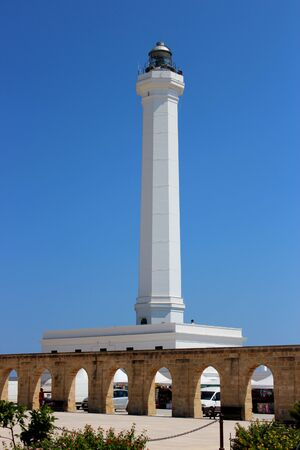 The Basilica of Santa Maria de finibus terrae in the town of Santa Maria di Leuca, in Salento, Puglia, Lecce, Italy. The blue sky and lighthouse. The statue of the Madonna on top of a column, obelisk. Stock fotó