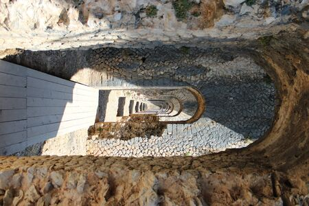 The Temple of Jupiter, Mount Circeo, in Terracina, Lazio, Italy. The remains of the temple on the top of the mountain. A series of consecutive arches and columns create a tunnel.