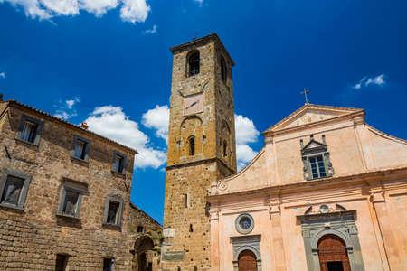 Civita di Bagnoregio, Viterbo, Tuscia, Lazio, Italy. The Church of San Donato with the bell tower and the clock. Three wooden doors.