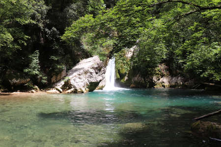 The waterfall of San Benedetto in Subiaco, Rome, Lazio, Italy. Cool place, refreshment from summer heat. Trekking, mountain excursion. Peace, silence, nature. Some people sunbathe on the rocks.