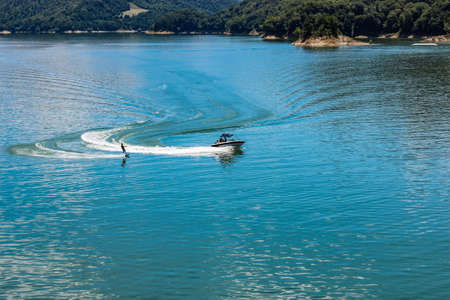 The lake of Salto, the largest artificial lake in Lazio, in the province of Rieti and created by damming the Salto river with the Salto dam. A sportsman practices water skiing towed by a motorboat.