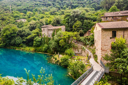 A glimpse of the small village of Stifone, on the Nera river. Umbria, Terni, Italy. The walls of stones and bricks. The bridge over the river with clear blue waters. Tourists stroll through the alleys