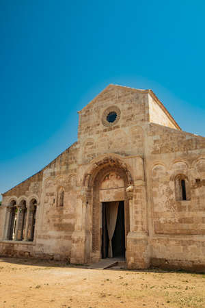 August 10, 2021 - Abbey of Santa Maria a Cerrate, Puglia, Salento, Lecce - Ancient Romanesque church, heritage of the FAI. The facade with the large arch above the portal and the columns on the sides. Editorial
