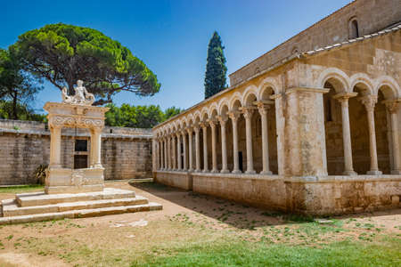 August 10, 2021 - Abbey of Santa Maria a Cerrate, Puglia, Salento, Lecce - The portico at the side of the church, shady and cool, with arches and columns. Shelter from the sun and the summer heat. Editorial