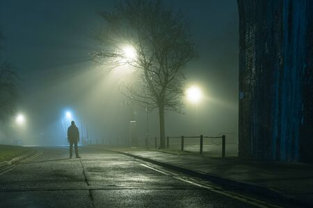 A mysterious figure standing by a city street light on a moody,  foggy atmospheric winters night