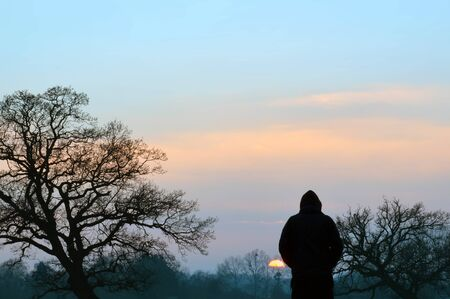 A silhouette of a hooded figure standing in a field, watching the sunset on a winters afternoon.