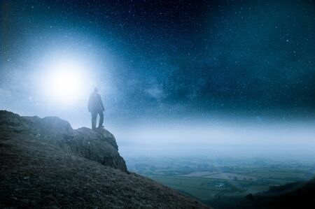 A night sky full of stars edit. With a lone man with a rucksack on a hill with light flare.