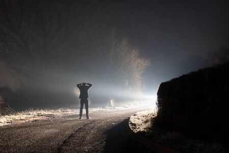 A figure standing on a road surrendering with his hands on his head. Looking at a bright light.  On a spooky country lane. On a misty winters night.