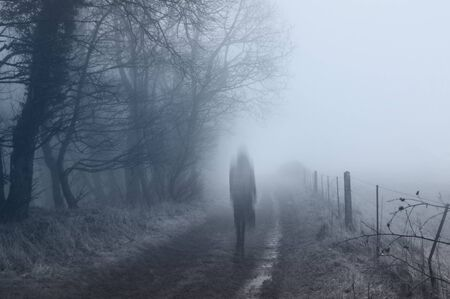 A ghostly woman walking along a country path on a spooky misty winters day. With a cold, blue edit.