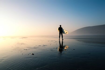 A surfer holding a surfboard silhouetted against the setting sun, on a misty winters day. Saunton, Devon, UK. Standard-Bild
