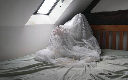 A spooky, ghostly figure sitting on a bed, with a hand reaching out in pain