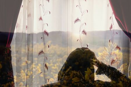 A double exposure of a hooded figure, looking out of a window with a picture of the setting sun and yellow gorse flowers.. Signifying mental health and isolation issues.