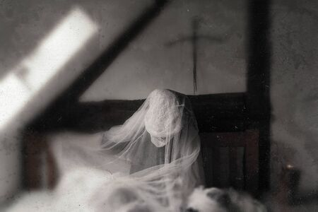 A ghost like figure, sitting on a bed in a corner of an old timber framed building. With a blurred, textured, weathered, abstract edit.