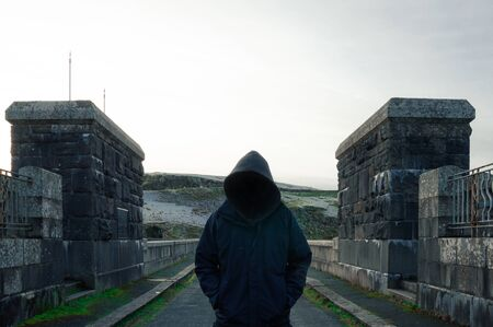 A scary, hooded figure with a blank black space where his face should be, standing on a road in the countryside in winter