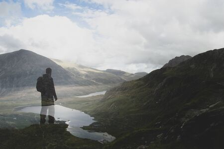 Hiker with backpack standing on top of a hill looking at a lake and mountains. With a double exposure edit. Snowdonia, Wales, UK. Banco de Imagens
