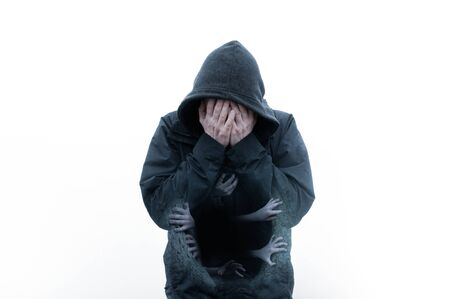 A mental health, horror concept of a double exposure of a moody, hooded figure, head in hands. With hands coming out of his chest.