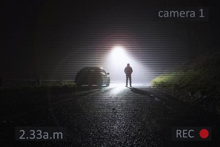 A car parked on the side of the road, underneath a street light, with a hooded figure, on a rural, country road. On a foggy winters night. With a CCTV surveillance edit.