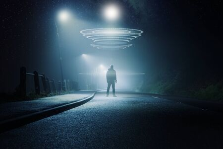 A science fiction concept. A mysterious figure standing in the middle of a road. On a foggy winters night. With bright UFOs glowing above his head.